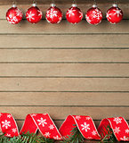 Ribbon and baubles on wooden background