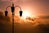 Silhouette of black street lamp against the background beautiful expressive cloudy sky.