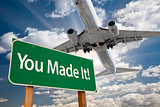 You Made It Green Road Sign and Airplane Above