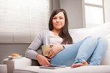 relaxed woman having breakfast in living room