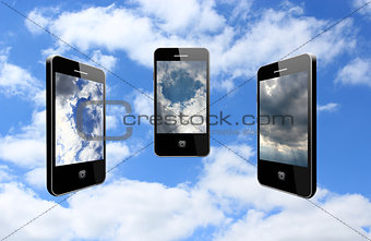 three modern mobile phones on the cloudy sky