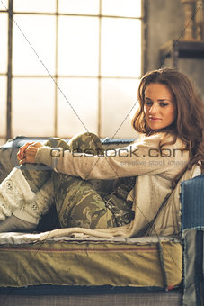 Thoughtful young woman sitting in loft apartment