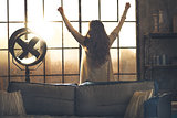Young woman looking in window in loft apartment and rejoicing. r
