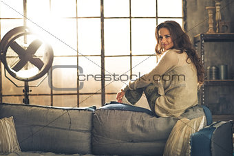 Portrait of young woman sitting in loft apartment