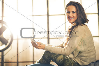Portrait of happy young woman with tablet pc in loft apartment