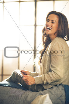 Portrait of smiling young woman using tablet pc in loft apartmen