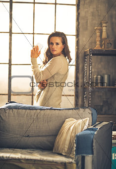 Portrait of young woman with cell phone in loft apartment