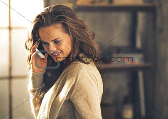 Portrait of young woman talking cell phone in loft apartment