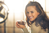 Portrait of happy young woman with cup of hot beverage