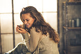 Portrait of relaxed young woman with cup of coffee in loft apart