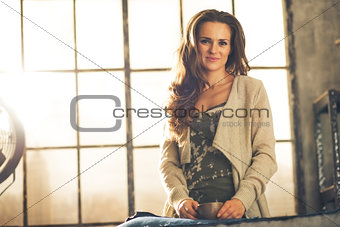 Portrait of happy young woman with cup of coffee in loft apartme