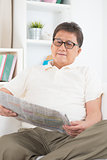 Mature Asian man reading newspaper