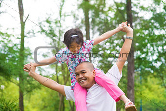 Asian Muslim father and daughter piggyback
