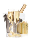 Champagne bottle in ice bucket, two glasses and christmas gift