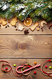 Christmas wooden background with snow fir tree, spices, gingerbr