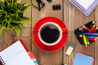 Office table with flower, supplies and coffee cup