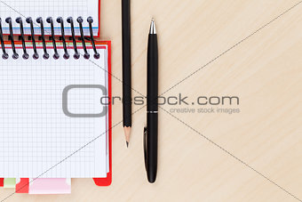 Office table with blank notepad, pen and pencil