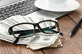 Office table with pc, coffee cup and glasses over money cash