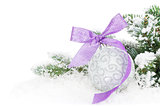 Christmas bauble and purple ribbon with snow fir tree