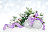 Christmas baubles and purple ribbon over snow bokeh background