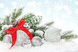 Christmas baubles and red ribbon over snow bokeh background