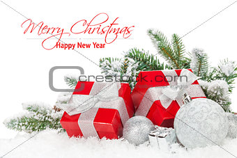 Christmas baubles and red gift boxes with snow fir tree