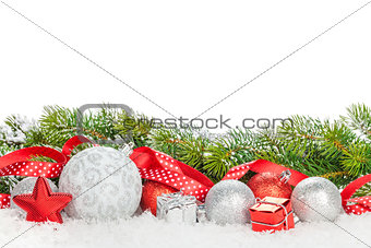 Christmas baubles and red ribbon with snow fir tree