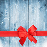 Red ribbon with bow over christmas snow wood background