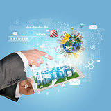 Man hands using tablet pc. Business city on touch screen. Earth with buildings near computer