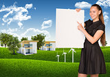 Businesswoman holding empty paper. House and nature landscape