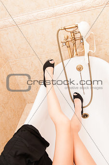 Skinny female sexy legs in bath tub with bra on tap