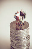 Minatue family on pile of coins. Family budget concept. Macro photo with retro style effect