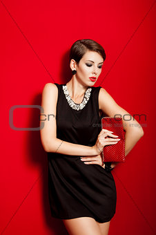Beautiful girl with a red clutch bag