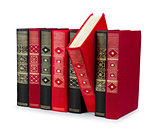 stack of vintage red and black books with gold ornament on a whi