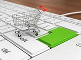 Shopping trolley over keyboard. E-market concept.