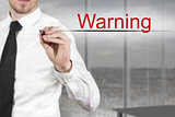 businessman writing warning in the air