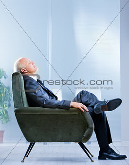 business man on an armchair with eyes closed