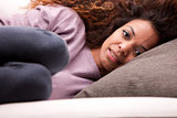 beautiful african-american woman lying on a sofa