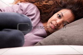 beautiful african-american woman lying on a sofa