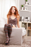Red Headed very cute girl sitting on her sofa