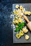 Homemade raw Italian tortellini and basil leaves