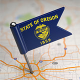 Oregon Small Flag on a Map Background.