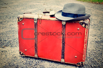 Old suitcase with watch and hat