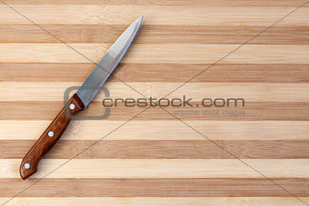 Kitchen knife on wooden board