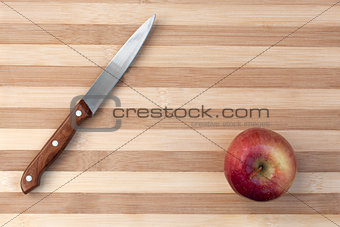 Knife and apple on wooden table board