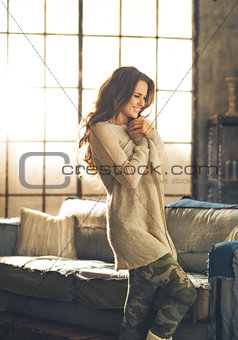 Portrait of relaxed young woman in loft apartment