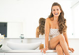 Happy young woman sitting in bathroom
