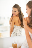 Happy young woman checking skin condition in bathroom