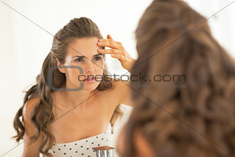 Portrait of young woman checking facial skin condition