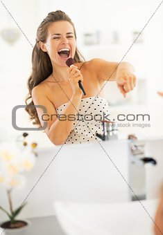 Portrait of happy young woman singing with makeup brush
